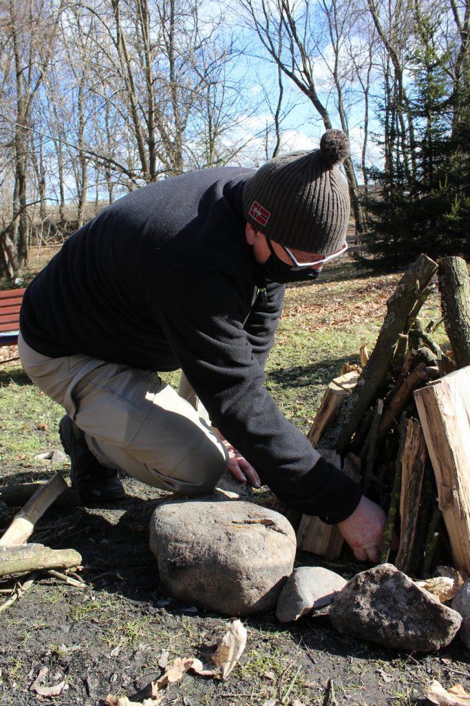 Mężczyzna odpala stos drewna (ognisko)