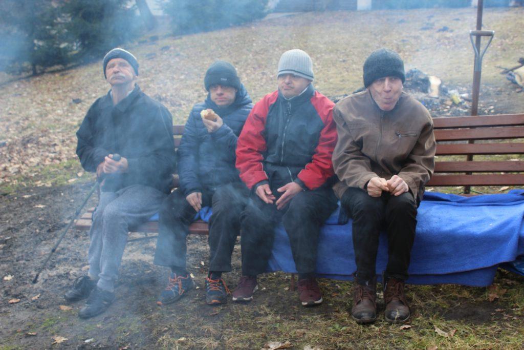 Czterech mieszkańców siedzących na ławce i jedzą
