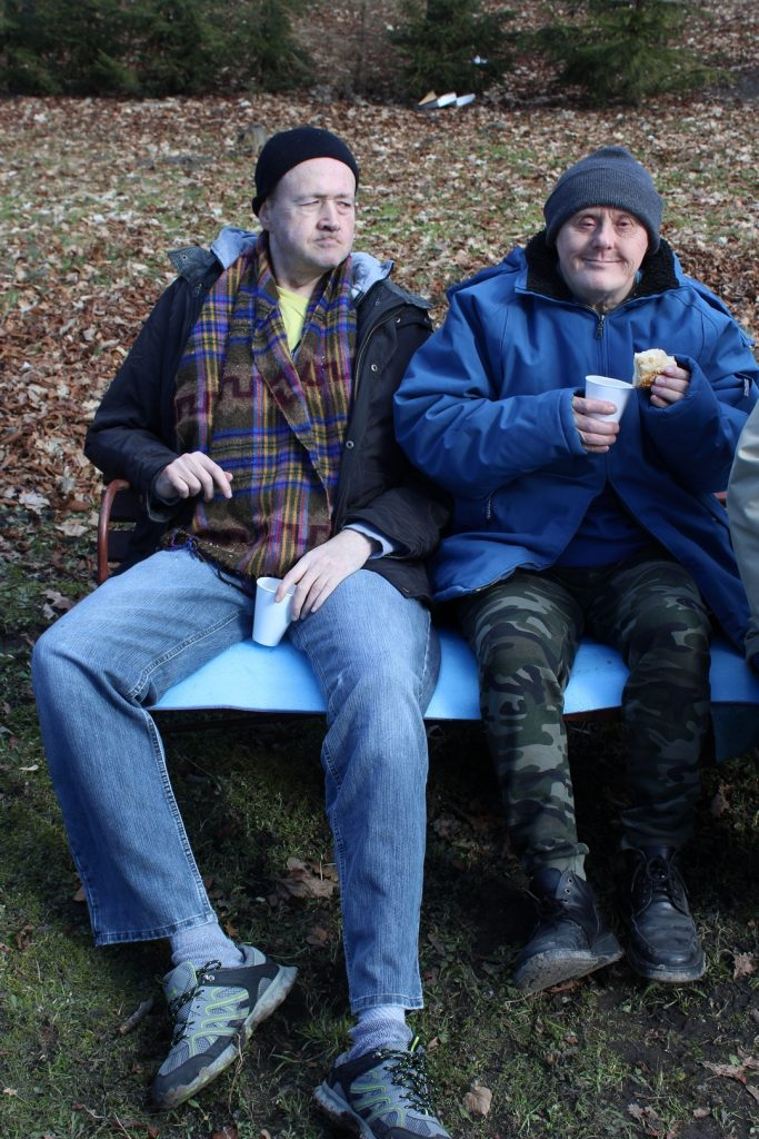 Mieszkańcy siedzą na ławce, w rękach trzymają kubki i jedzenie