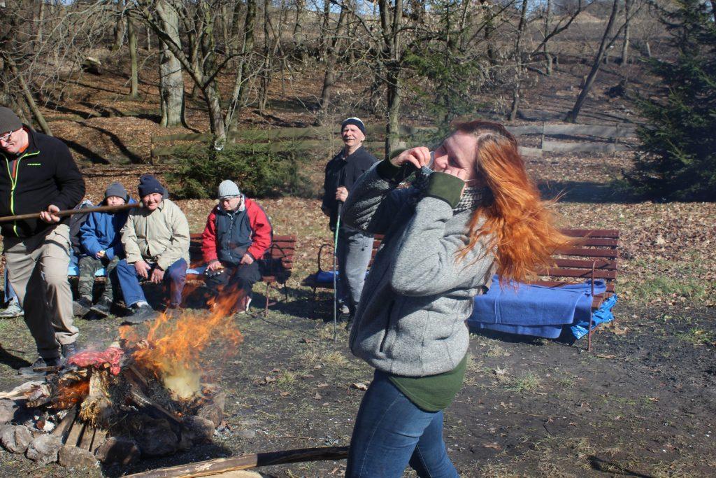 Kobieta z długimi rudymi włosami poprawia sobie maskę, w tle opiekun stojący nad ogniskiem w tle siedzą na ławce mieszkańcy