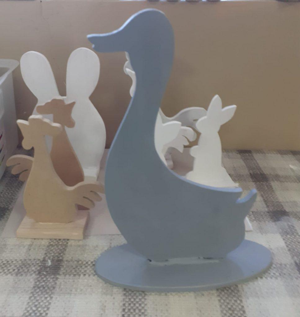 Zielona drewniana figurka kaczki na podstawce. W tle inne zwierzątka świąteczne wykonane z drewna