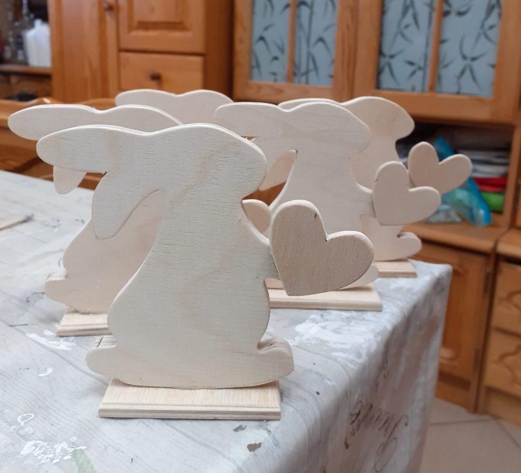 Drewniane króliczki na podstawkach w rękach trzymające drewniane serduszko