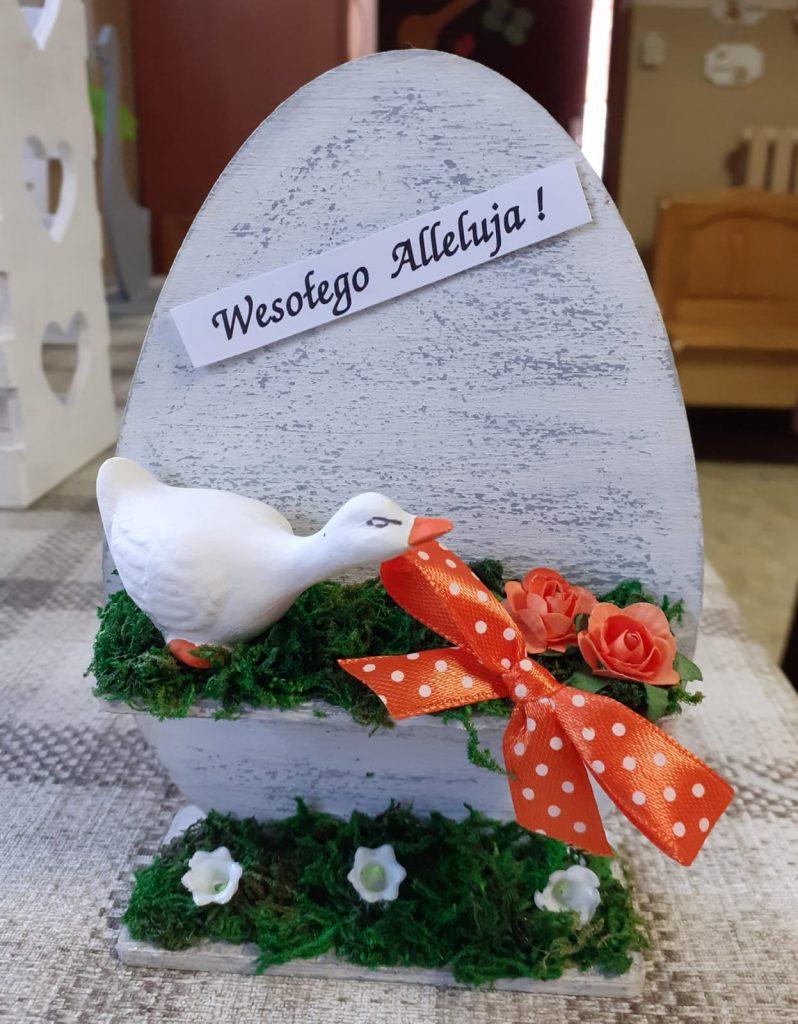 Szaro-białe jajko ozdobione małą drewnianą kaczką, czerwoną wstążką w białe kropki oraz kwiatkami i mchem.