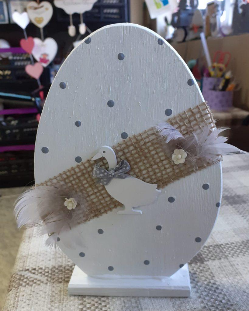 Białe jajko w szare kropki przepasane ozdobieniem z siatki, malutką białą kaczką