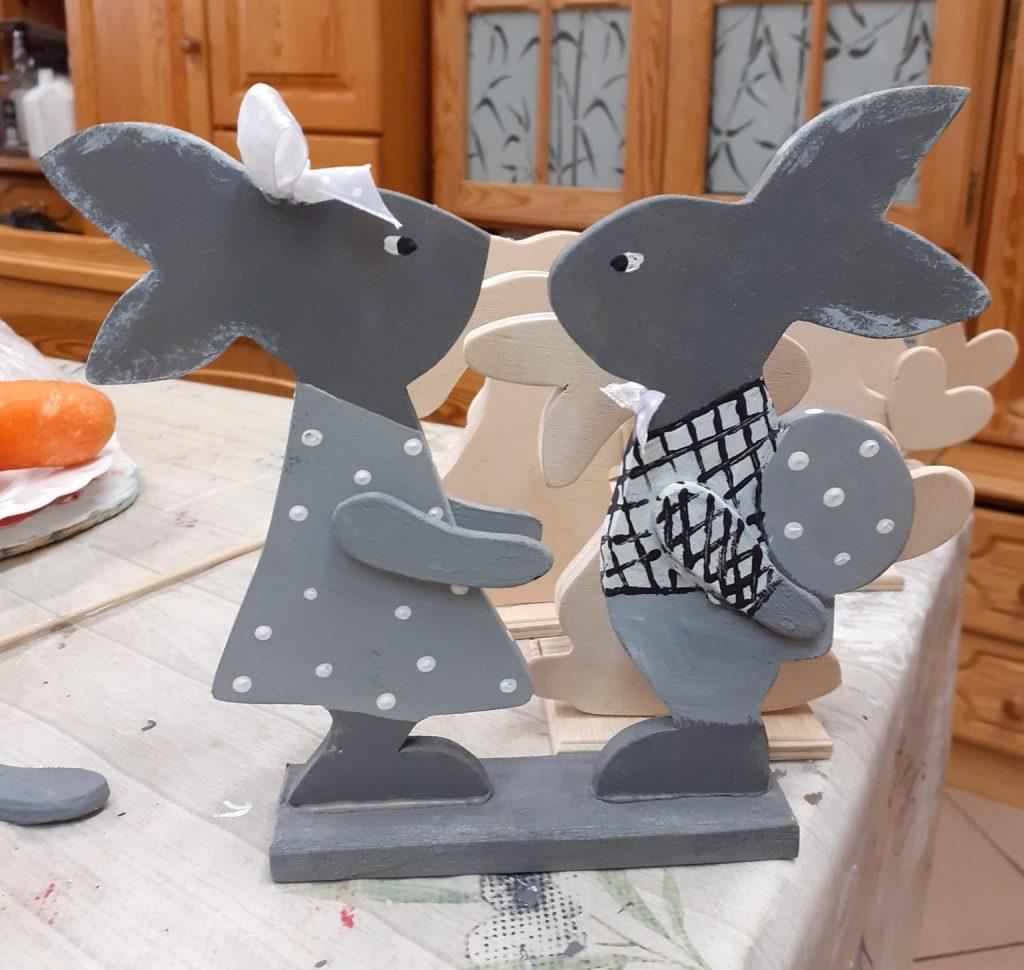 Dwa drewniane zajączki stojące na przeciw siebie jeden ma jasną kokardę na głowie, drugi trzyma jajko.