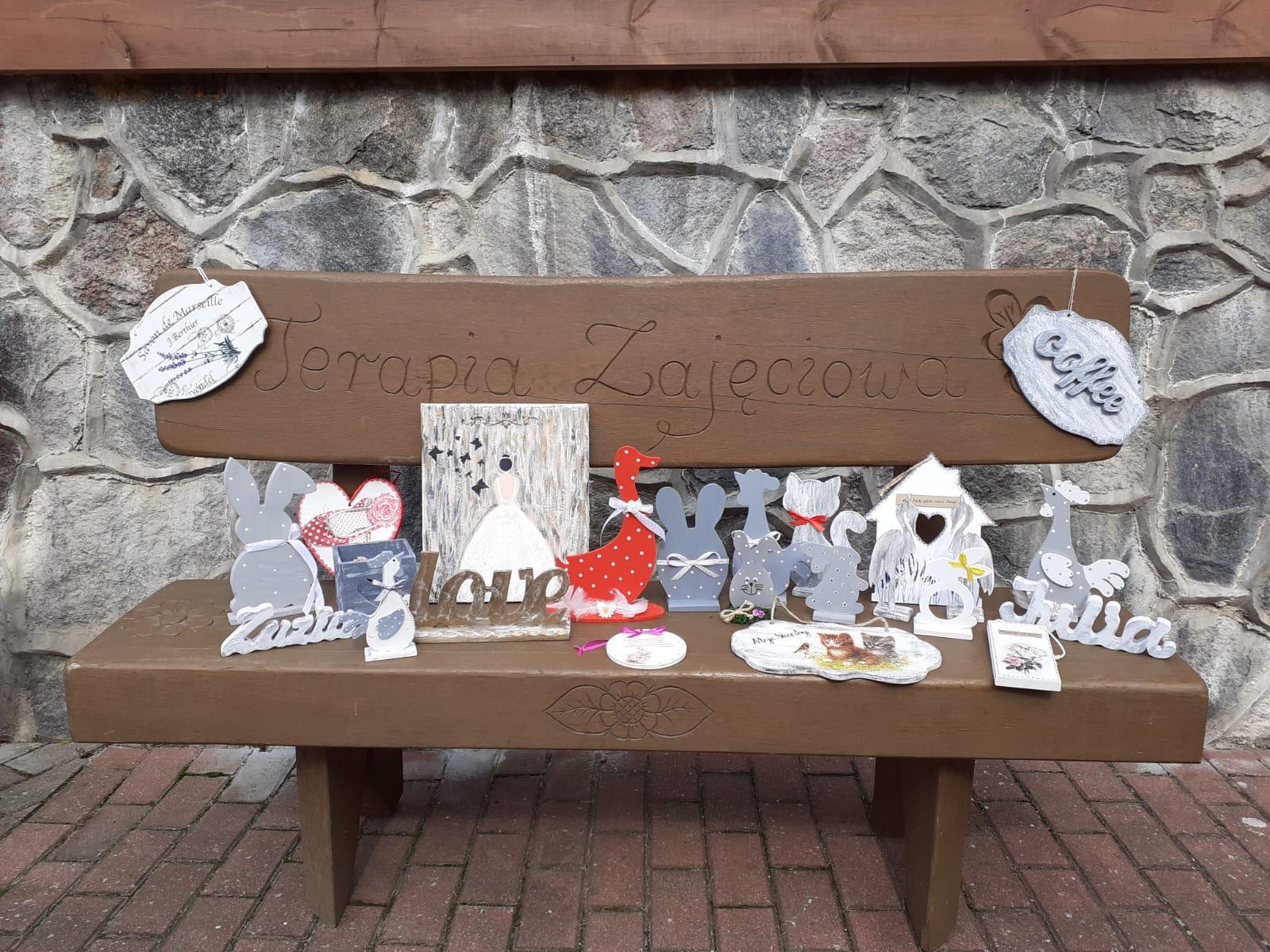 """Na drewnianej ławeczce z napisem """"terapia zajęciowa"""" leżą rękodzieła wykonane z drewna, kaczki, koguty, kotki, napis love i parę innych."""