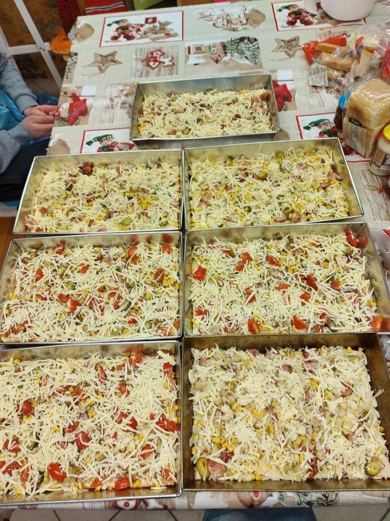7 dużych blach z pizzą na stole, pizzę posypane serem, blachy postawione obok siebie