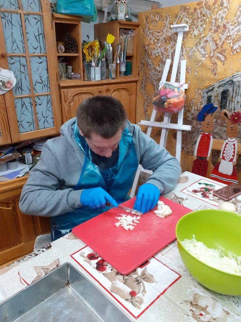 Mężczyzna siedzi przy stole, ubrane ma niebieskie rękawiczki do żywności, fartuch przeźroczysty i skrupulatnie kroi cebulkę, obok zielona miska wypełniona kawałkami pokrojonej cebuli
