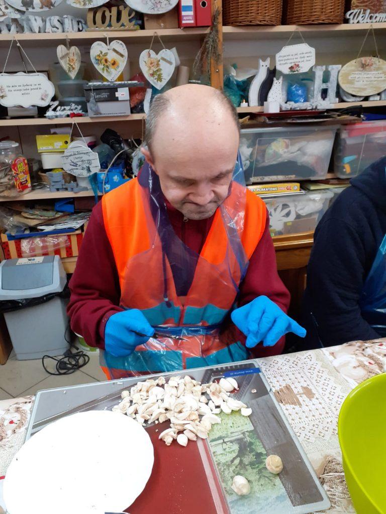Mężczyzna siedzi przy stole, ubrane ma niebieskie rękawiczki do żywności, fartuch przeźroczysty i kroi pieczarki