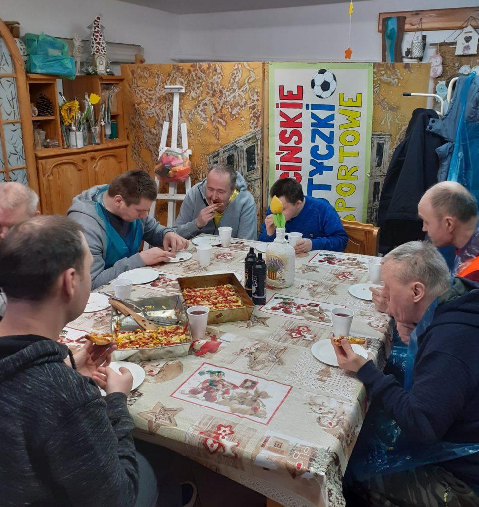 Siedmiu mieszkańców siedzących przy stole , jedzących własnoręcznie robioną pizzę, na stole dwie blachy pizzy, kubki z napojem i sosy