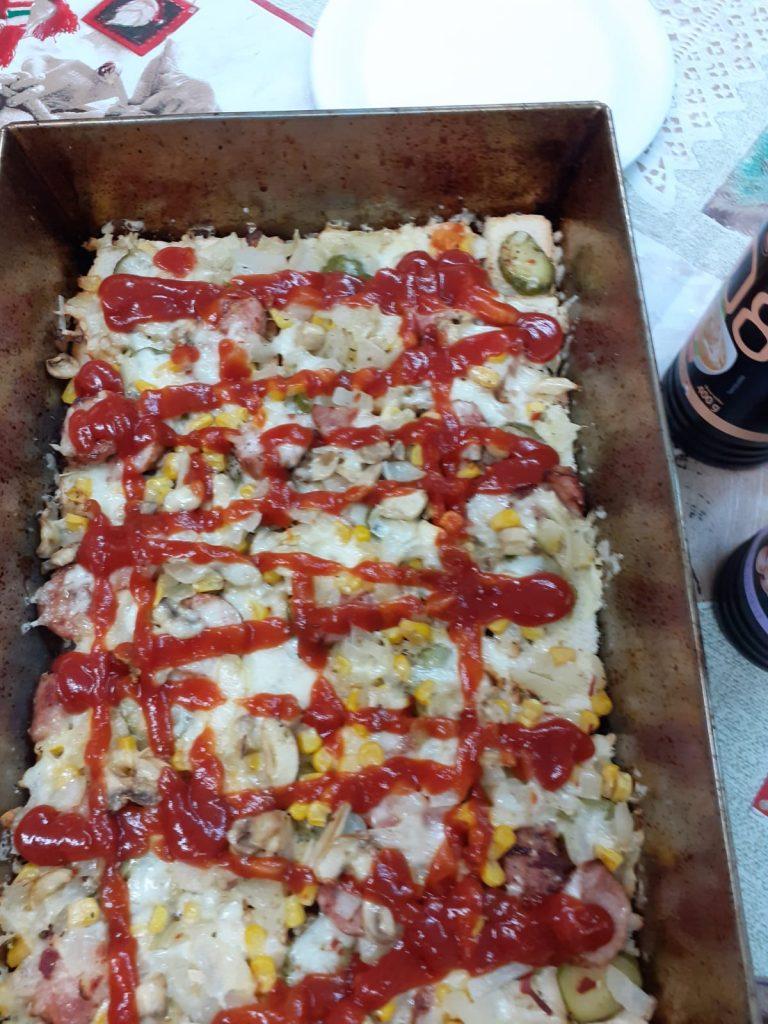 Metalowa blacha leżąca na stole, w której jest pizza polana czerwonym ketchupem