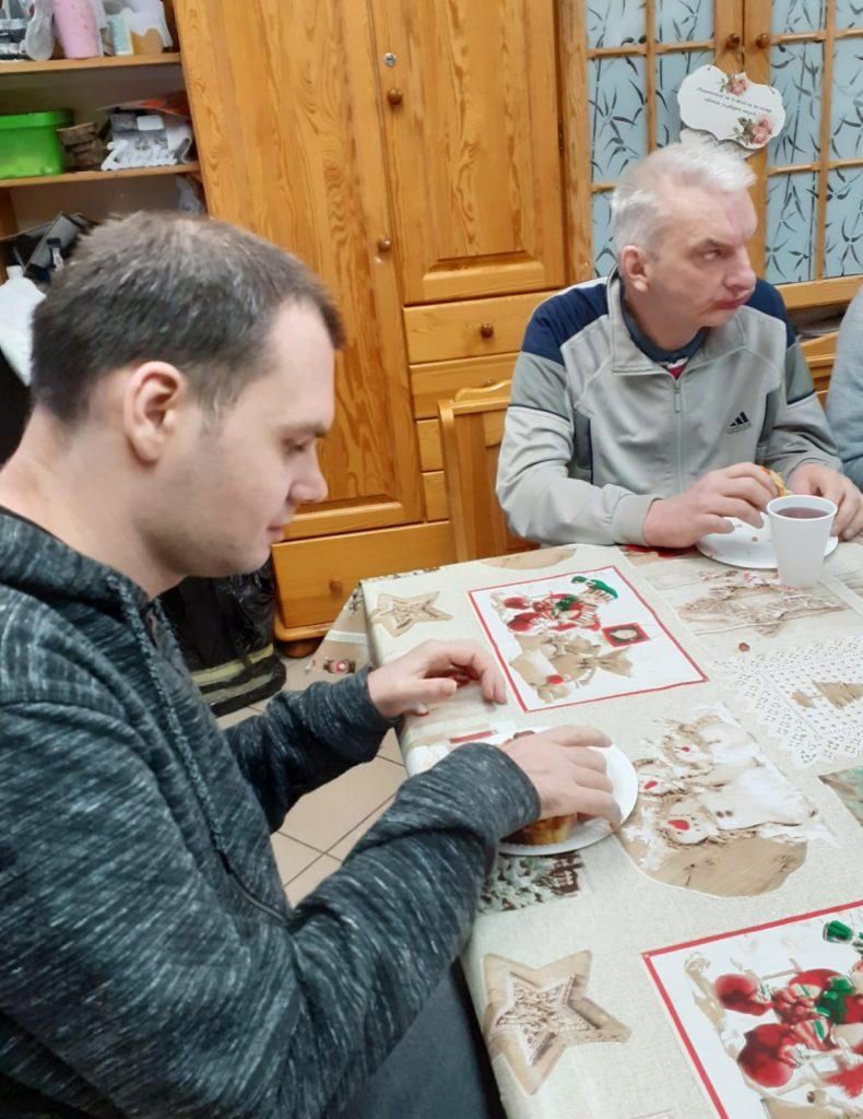 Dwóch mężczyzn w trakcie jedzenia posiłku, siedzą przy stole. Na stole kolorowa cerata.