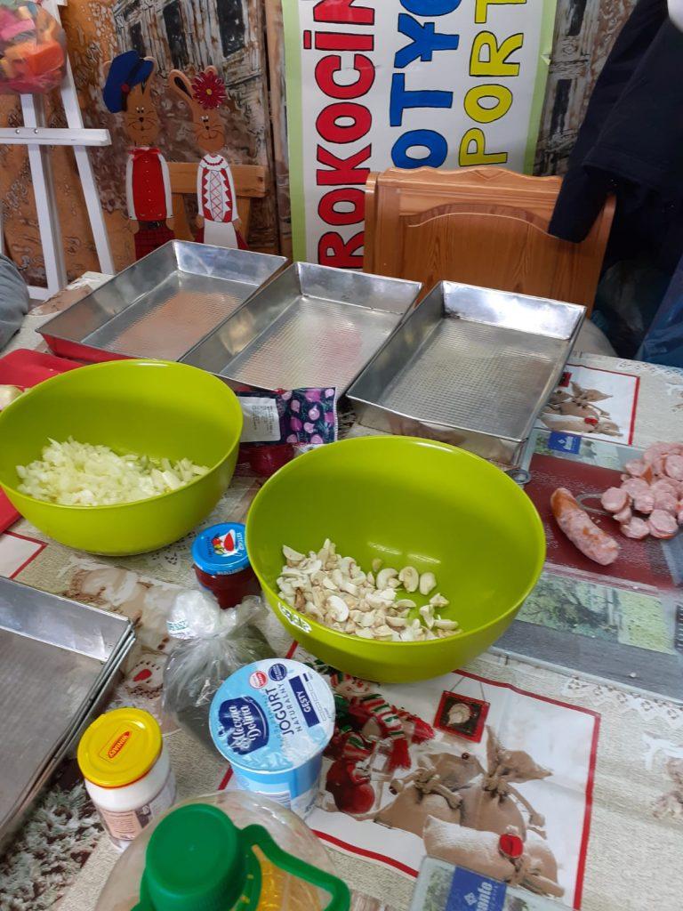 Na stole leżą trzy metalowe duże blachy, dwie zielone miski w jednej cebula w drugiej pieczarki, sosy i jogurt