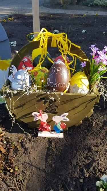 Drewniany koszyk wypełniony ozdobami, kolorowymi jajkami oraz kwiatami