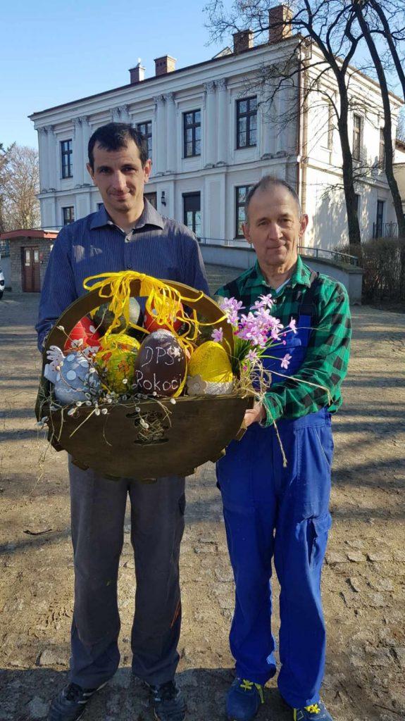 Dwóch mężczyzn trzymających wypełniony ozdobami drewniany koszyk w tle pałac