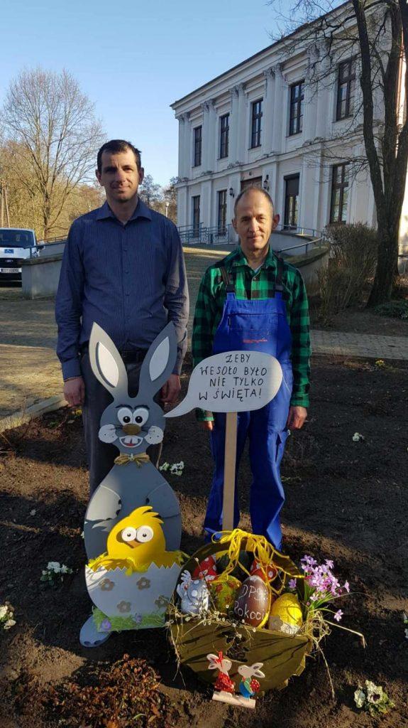 Dwóch mężczyzn stojących za drewnianym koszem z ozdobami, obok duży drewniany zająć a przed nim żółty mały kurczak w skorupce