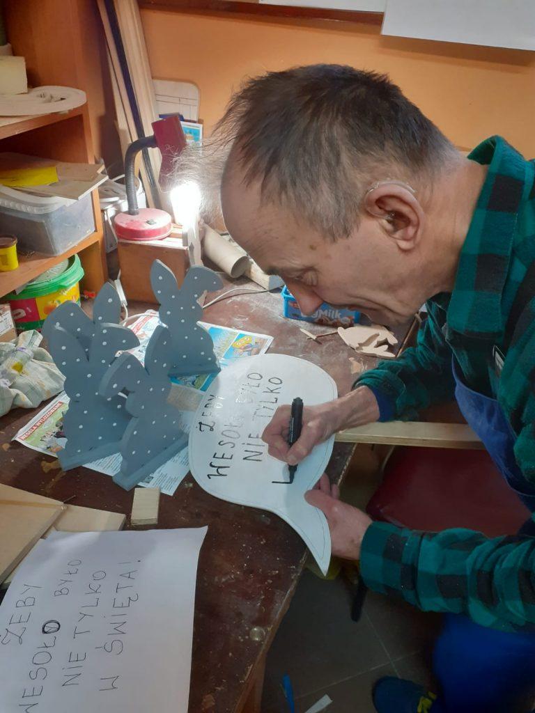 Pochylony mężczyzna maluje napis na drewnianej chmurce