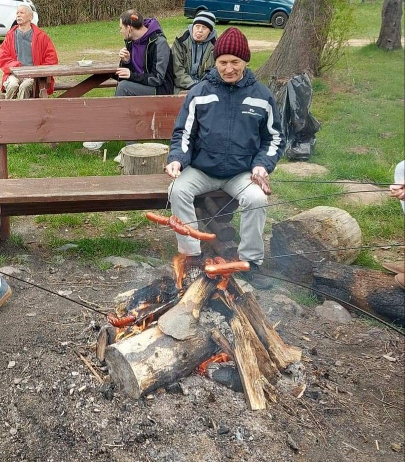 Mieszkaniec siedzi przy ognisku na drewnianej ławce w ręce trzyma kij z nabitą kiełbaską