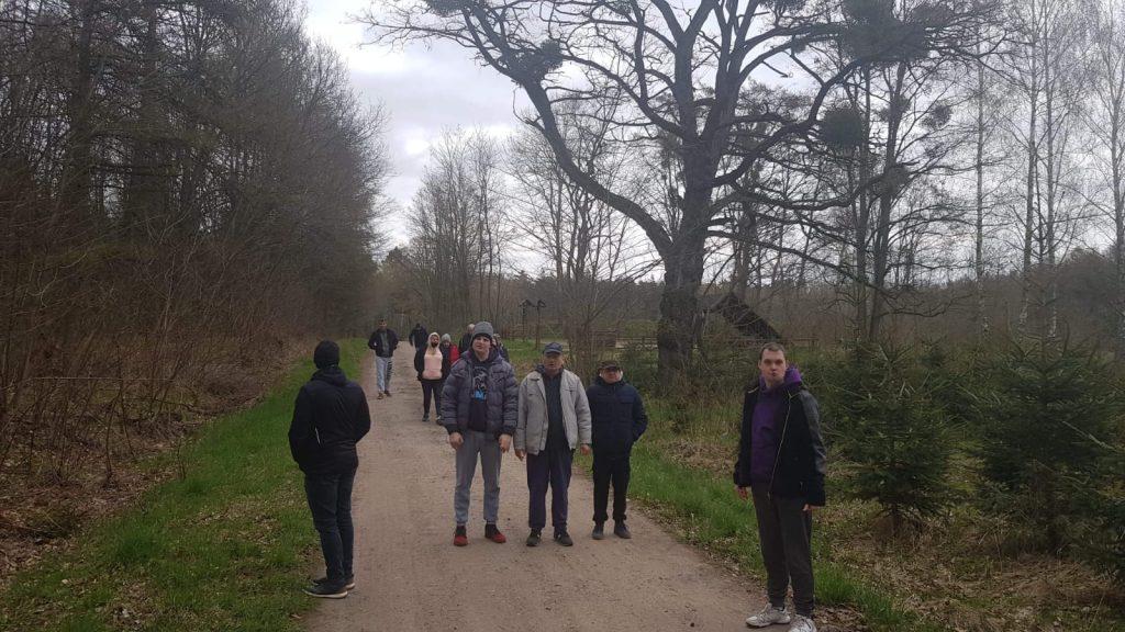 Grupa mieszkańców idąca ścieżką w lesie
