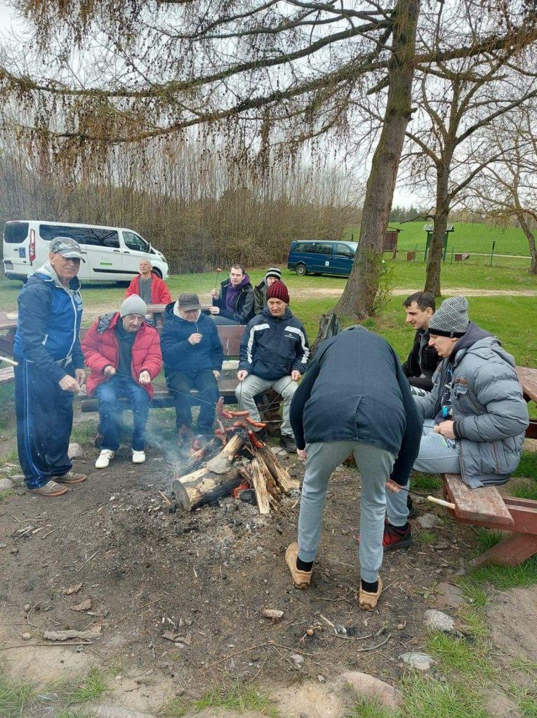 Grupa mieszkańców siedzących przy ognisku. Trzymają nad ogniskiem kije z nabitymi kiełbaskami.