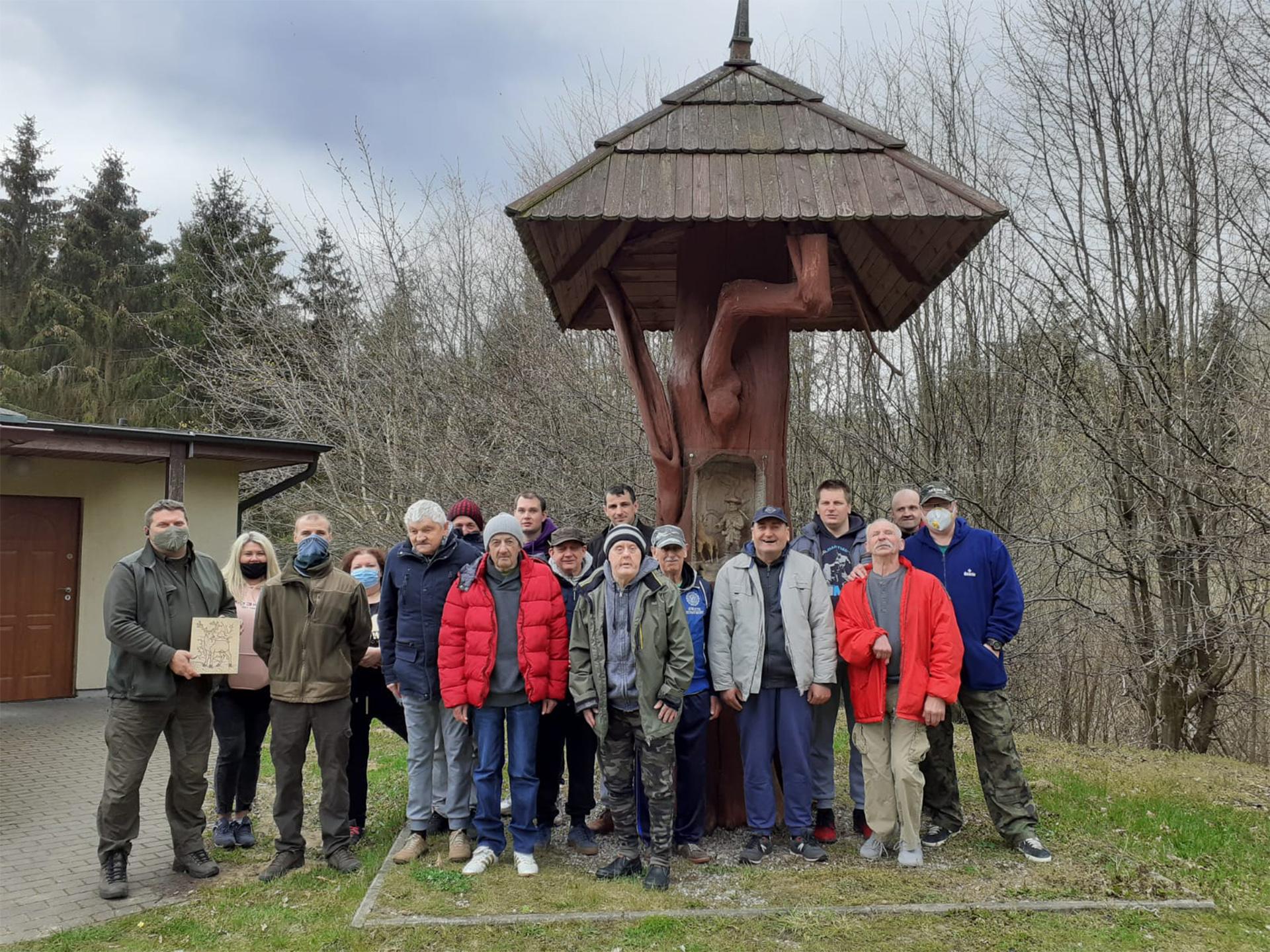 Grupa mieszkańców niedaleko leśniczówki, grupa stoi na dworzu