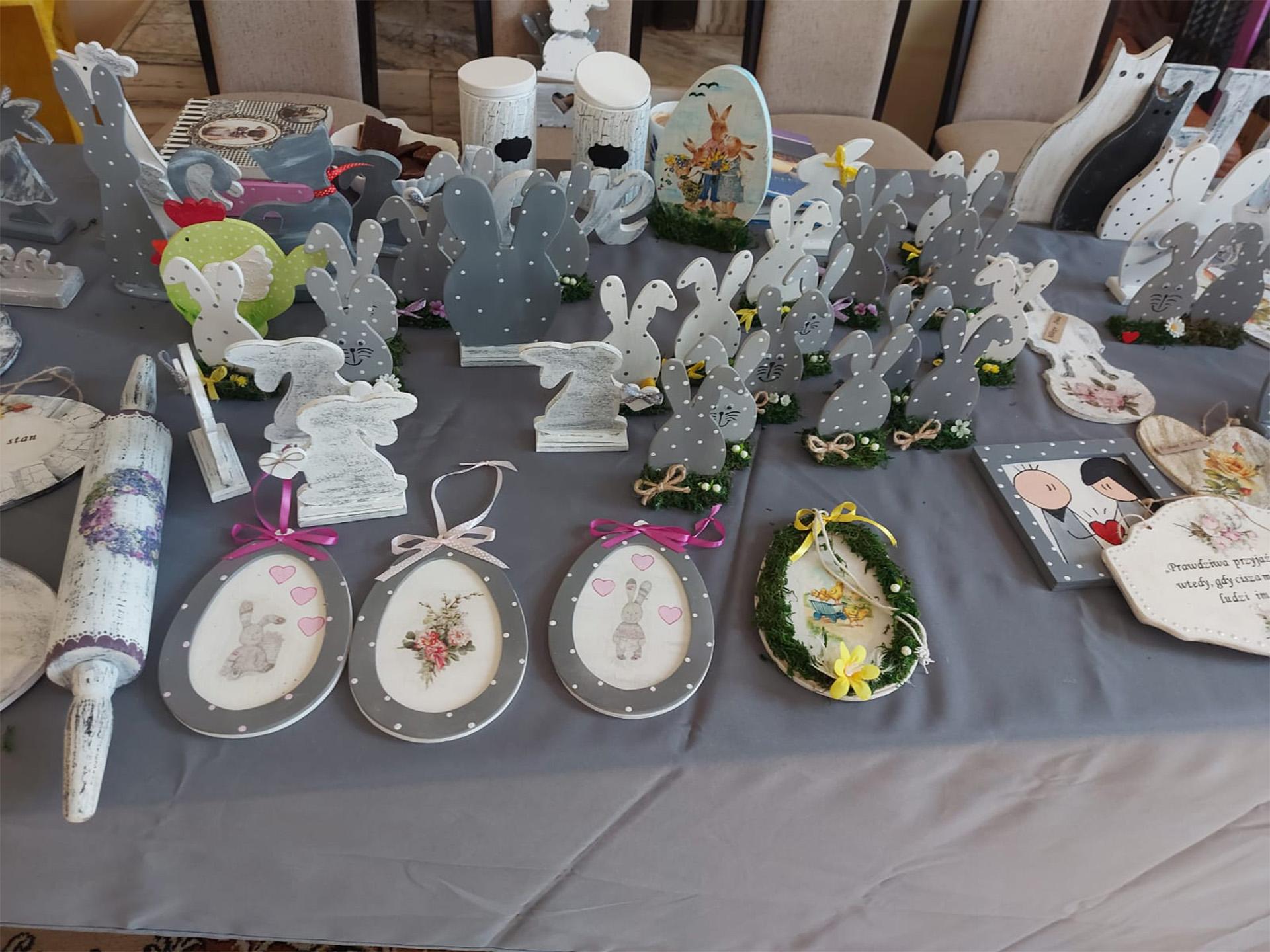 Stół na którym postawione są ozdoby zajączki, króliczki, koty, ozdoby do zawieszenia - wszystko w świątecznym Wielkanocnym klimacie