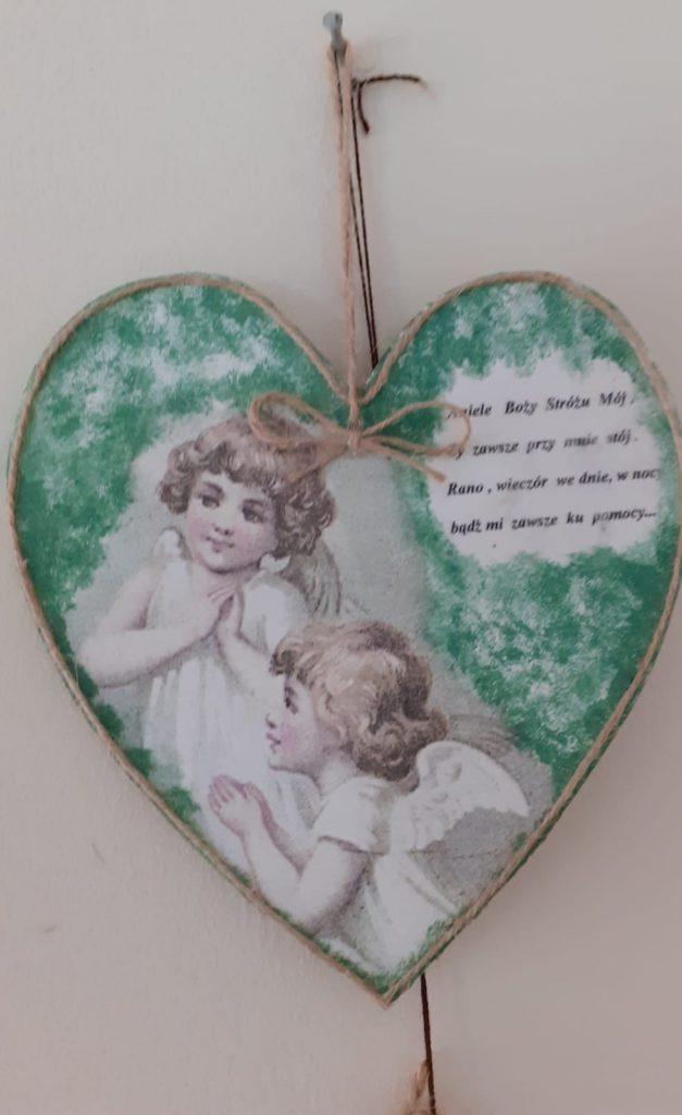 Drewniane serduszko z obrazkami anioła w środku