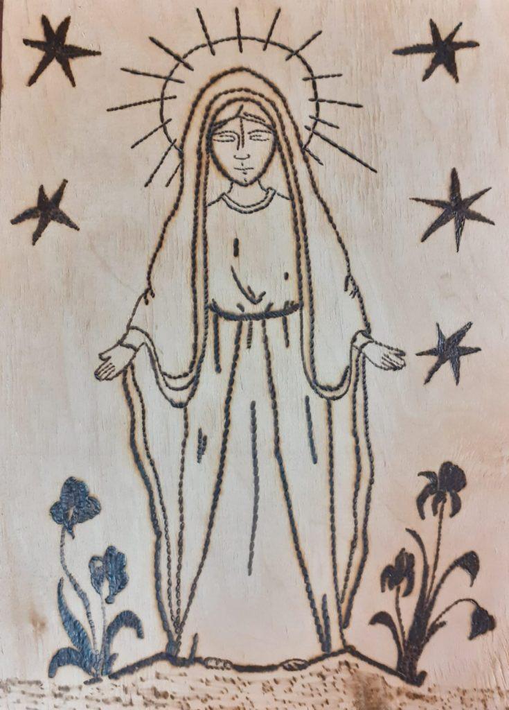 Wypalanka w drewnie przedstawia Matkę Boską wokół niej gwiazdy, a na ziemi po obu stronach kwiaty