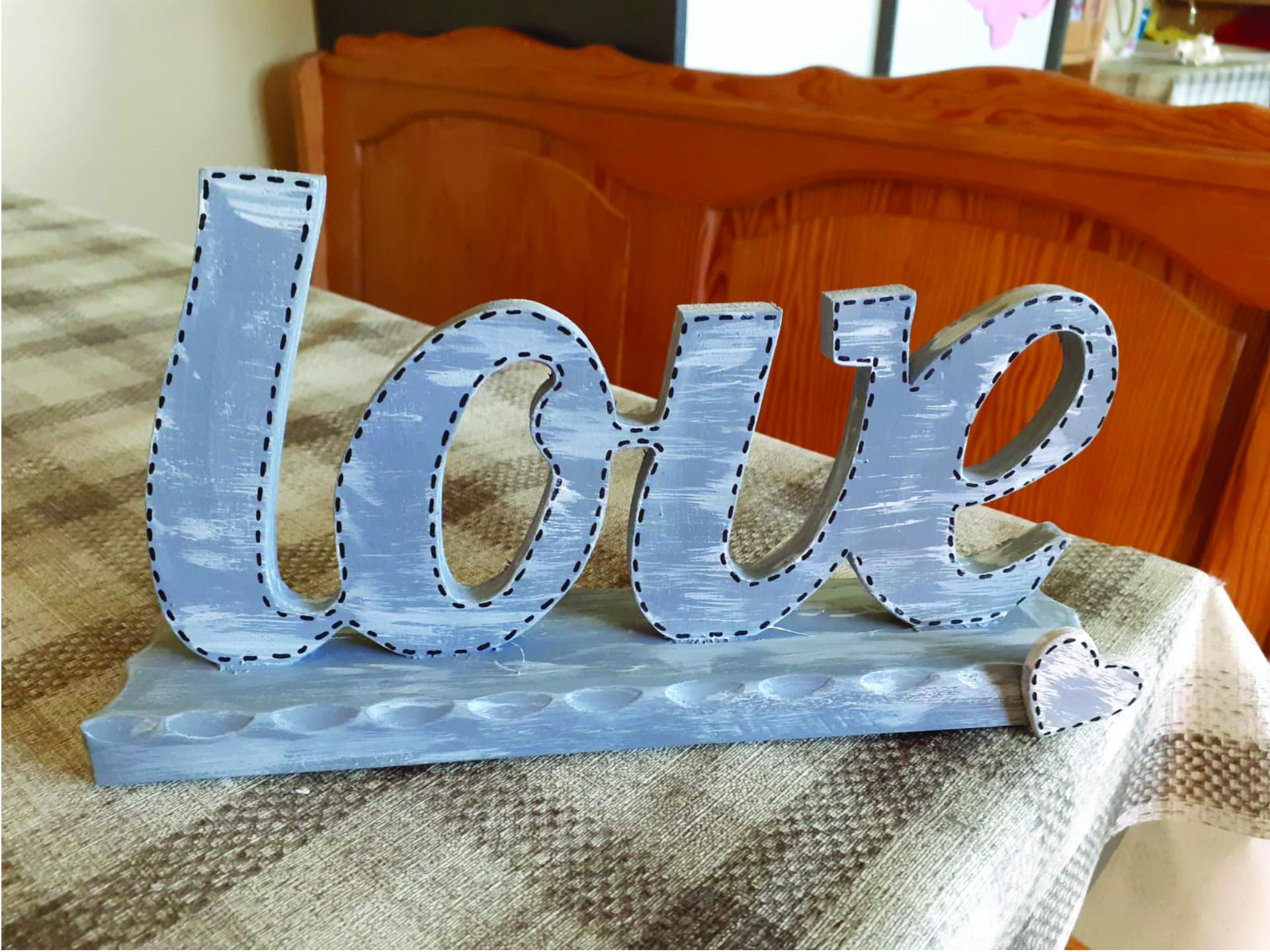 Drewniany napis LOVE na drewnianej cienkiej podstawce również wykonanej z drewna.