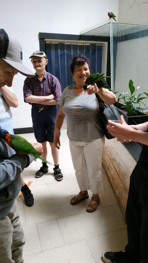 Uśmiechnięta opiekunka trzymająca papugę na  lewejręce