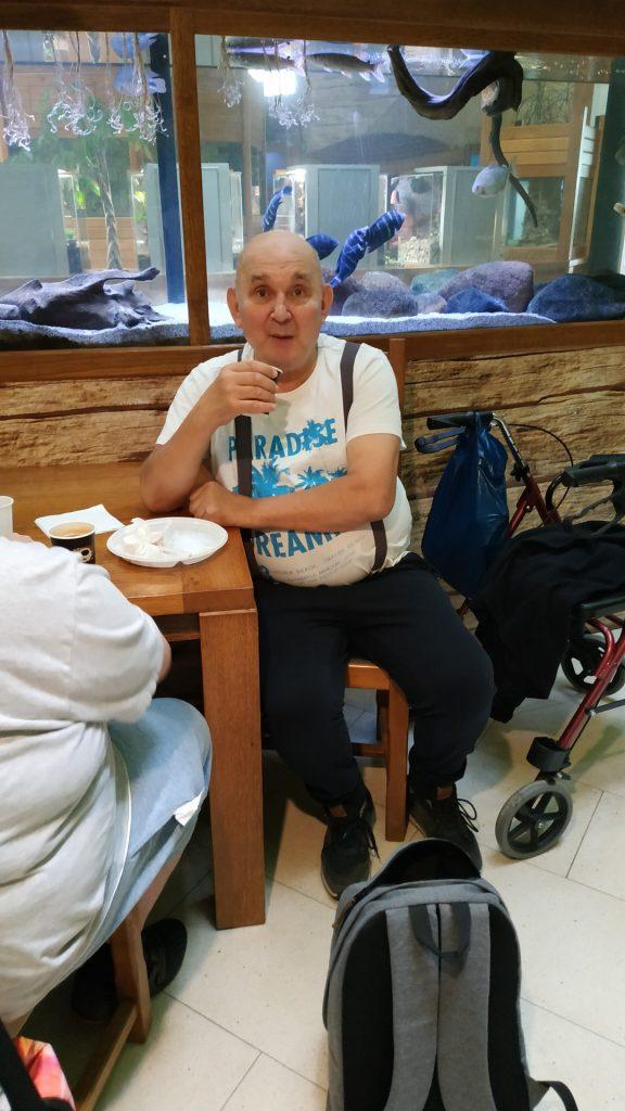 Mężczyzna siedzi przy stole na, którym jest pusty talerz, trzyma w ręce kubek z kawą, spogląda w stronę obiektywu. W tle duże akwarium