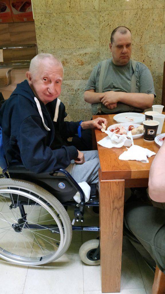 Podopieczny siedzi na wózku przy stole przy nim kolega. Oboje są w trakcie jedzenia.
