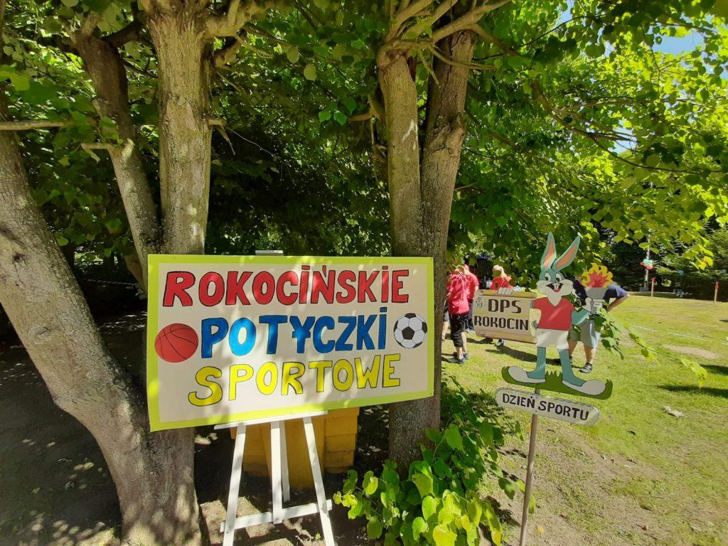 Kolorowy napis na tablicy Rokocińskie potyczki, tablica stoi na drewnianym stelarzu.