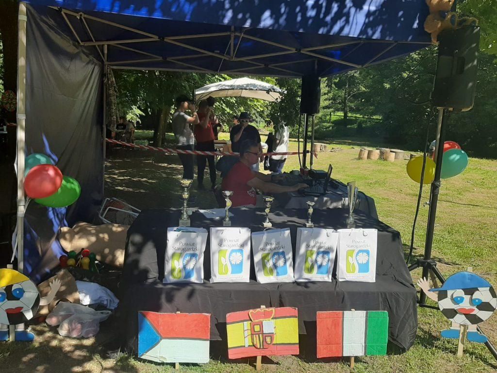 Opiekun puszczający muzykę pod namiotem, obok leżą nagrody sponsorowane przez powiat starogardzki niżej leżą flagi różnych państw