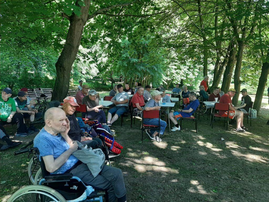 Grupa widzów siedzących na krzesłach w cieniu oraz wózkach inwalidzkich