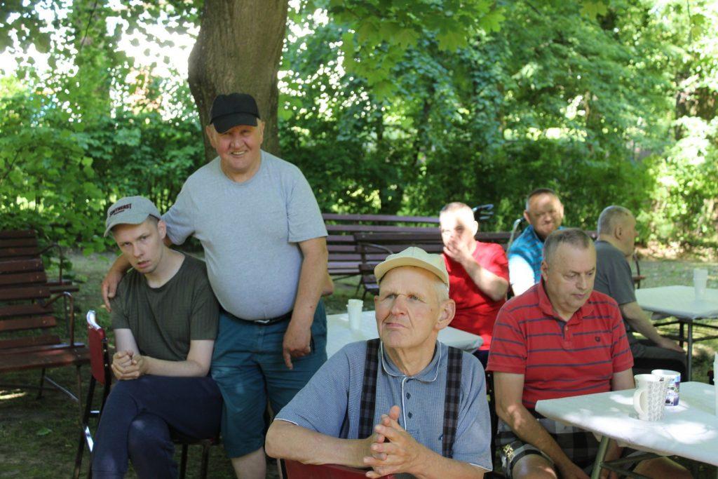 Grupa podopiecznych, jeden stoi i się uśmiecha, 6 innych siedzi przy stolikach w cieniu