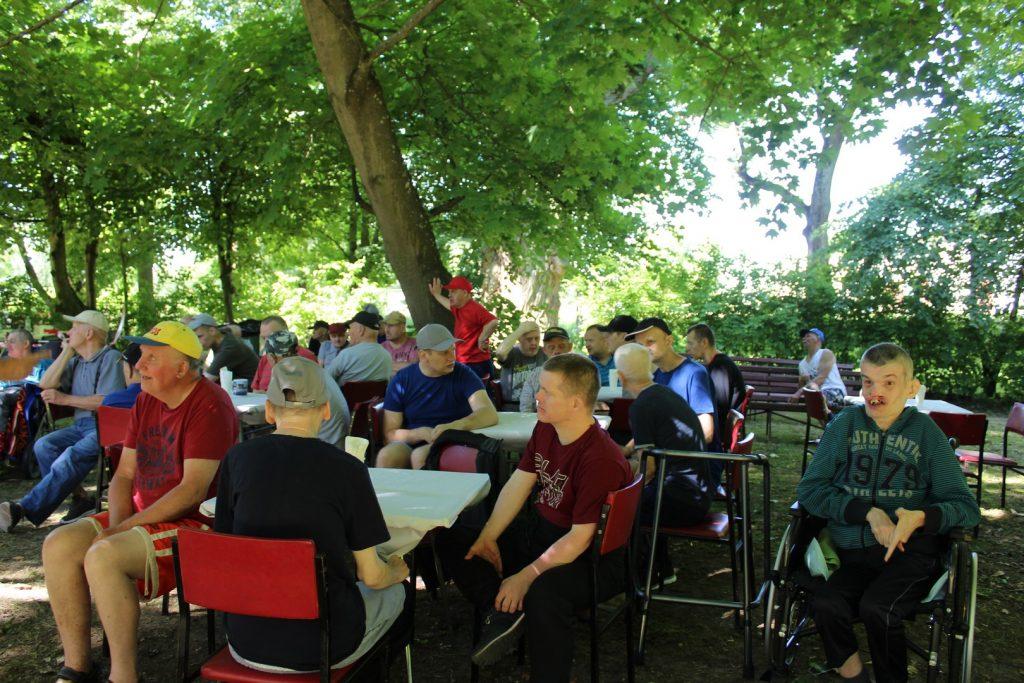 Wiele osób siedzących na krzesłach w cieniu między zielonymi drzewami