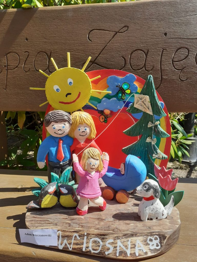 Rzeźba z drewna, przedstawia kolorowe postaci mężczyzny, kobiety, dziecka córeczki oraz dziecka w wózku obok pies a za nimi drzewo, słoneczko oraz tęcza.