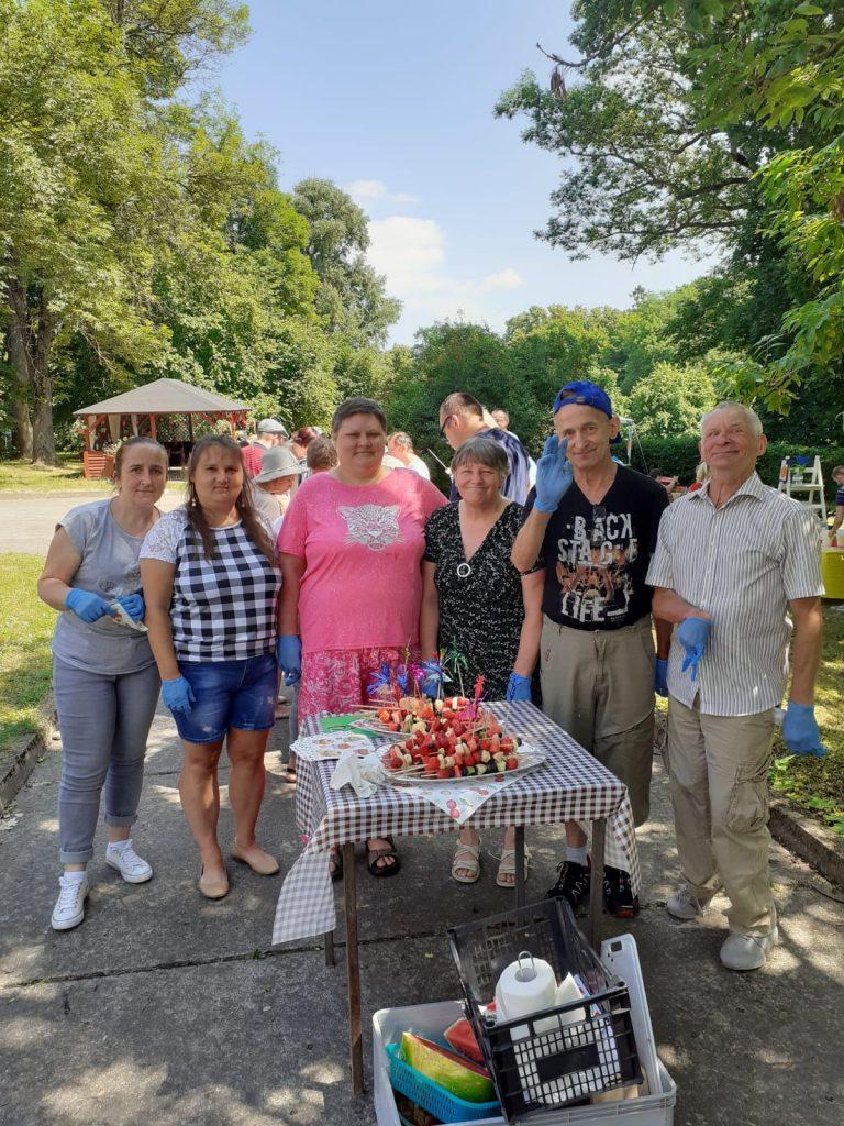 Cztery kobiety, dwóch mężczyzn stoją przed stołem, na stole dwa talerze owocowych szaszłyków