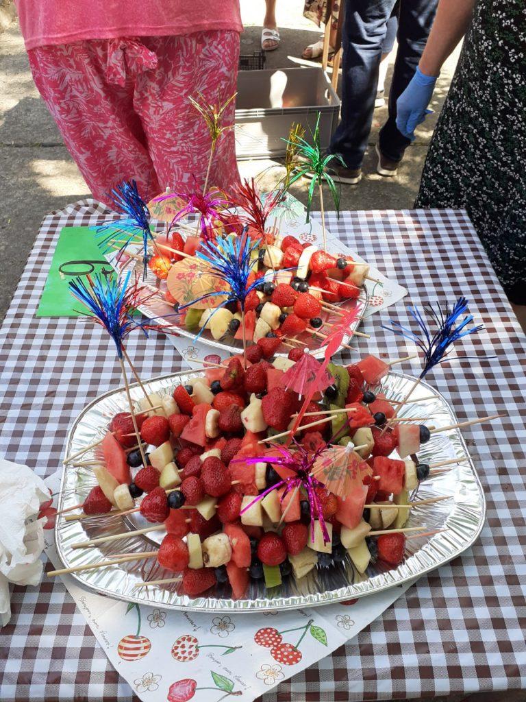 Stół z ceratą w kratę, na nim dwa duże talerze z owocowymi szaszłykami