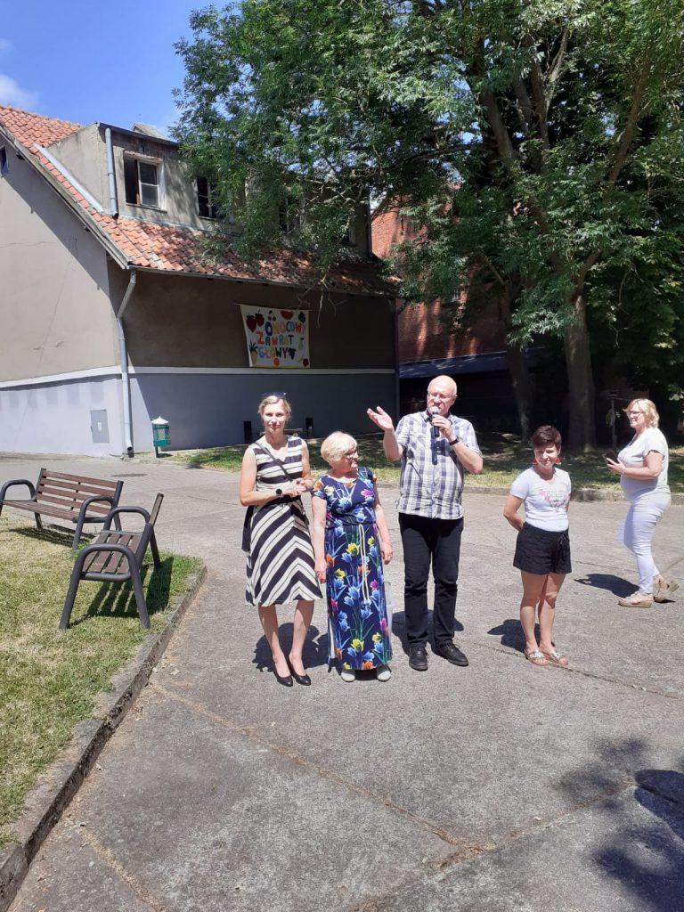 Cztery kobiety oraz jeden mężczyzna, który przemawia przez mikrofon. Za nimi budynek, obok dwie ławki