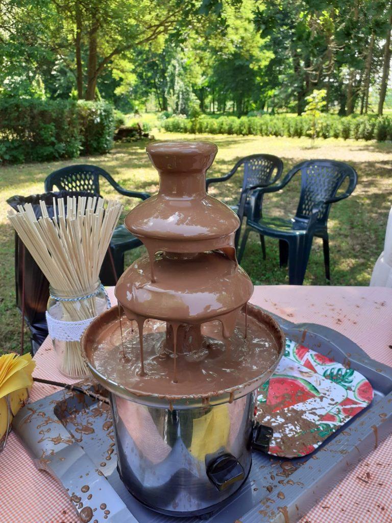 Fontanna z płynącą czekoladą, stoi na stole w tle krzesła