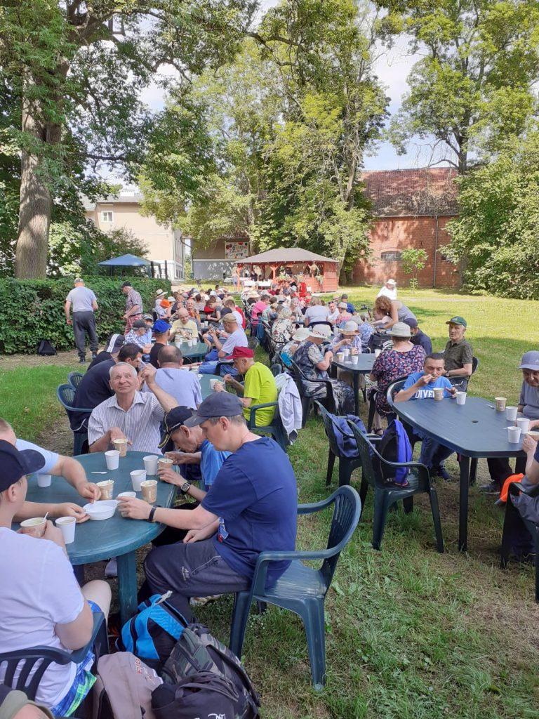 Grupa osób siedzących przy wielu stołach zajada owocowe szaszłyki, pije kawę, i spożywa obiad.