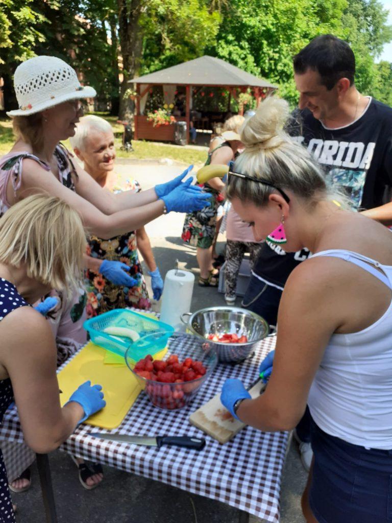 Grupa osób pracująca wspólnie, przygotowują szaszłyki.