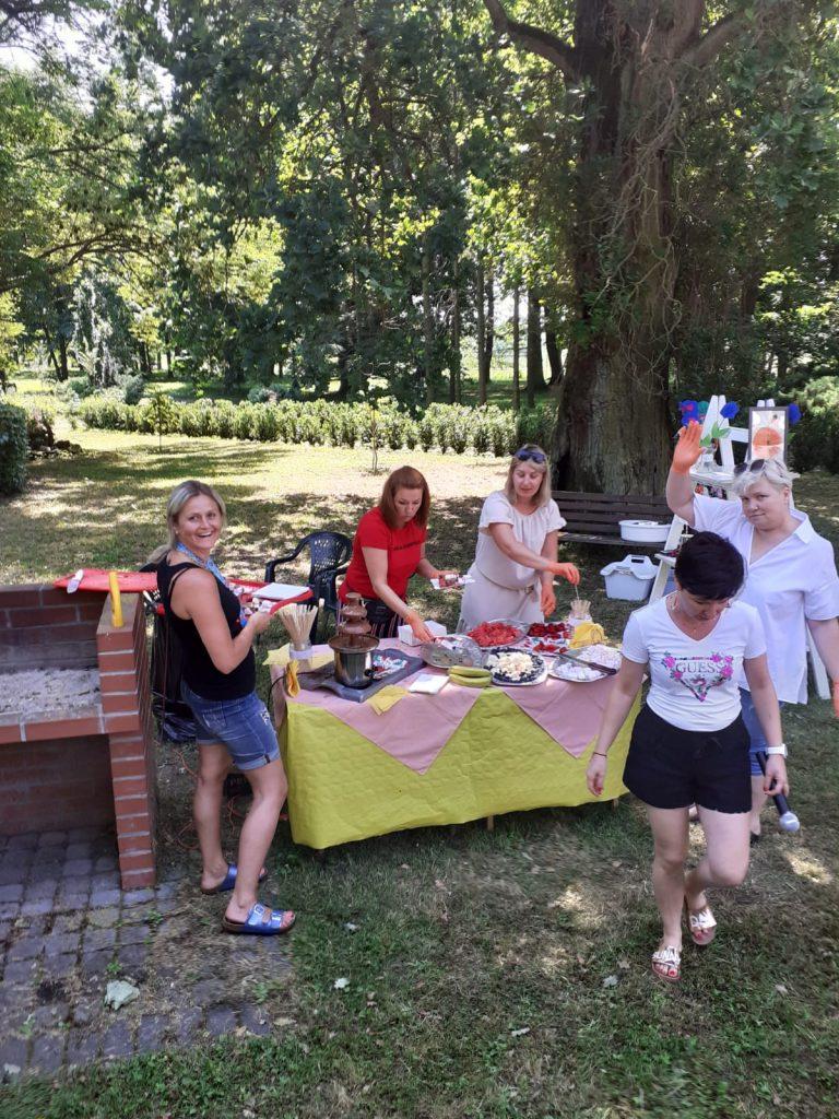 5 kobiet jedna uśmiecha się, druga kiwa, dwie stoją przy stole z szaszłykami w tle park