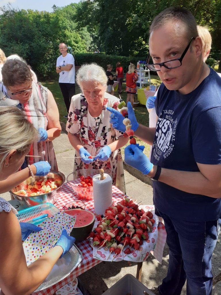 Grupa kobiet, oraz mężczyzna w niebieskich higienicznych rękawiczkach trzyma owocowy szaszłyk i spogląda w stronę obiektywu.