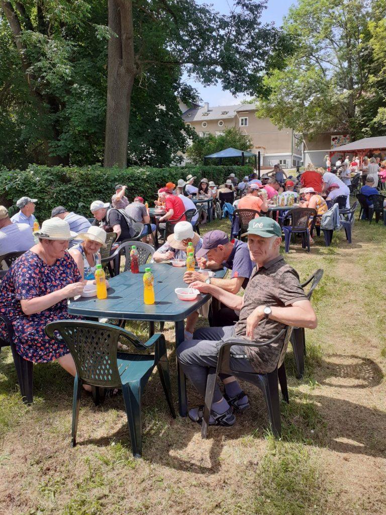Grupa osób siedzących na zielonej trawie przy stołach.  Spożywają posiłek.