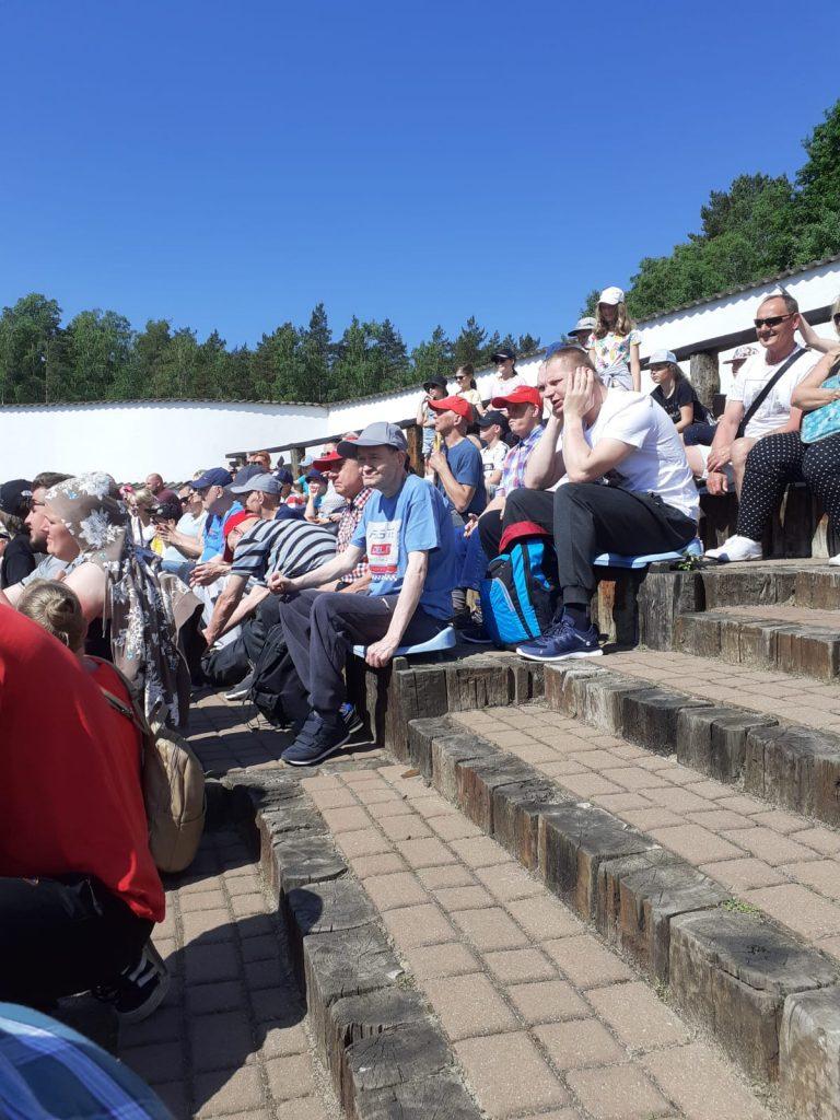 Grupa osób siedząca na podestach, nad głowami bezchmurne niebo