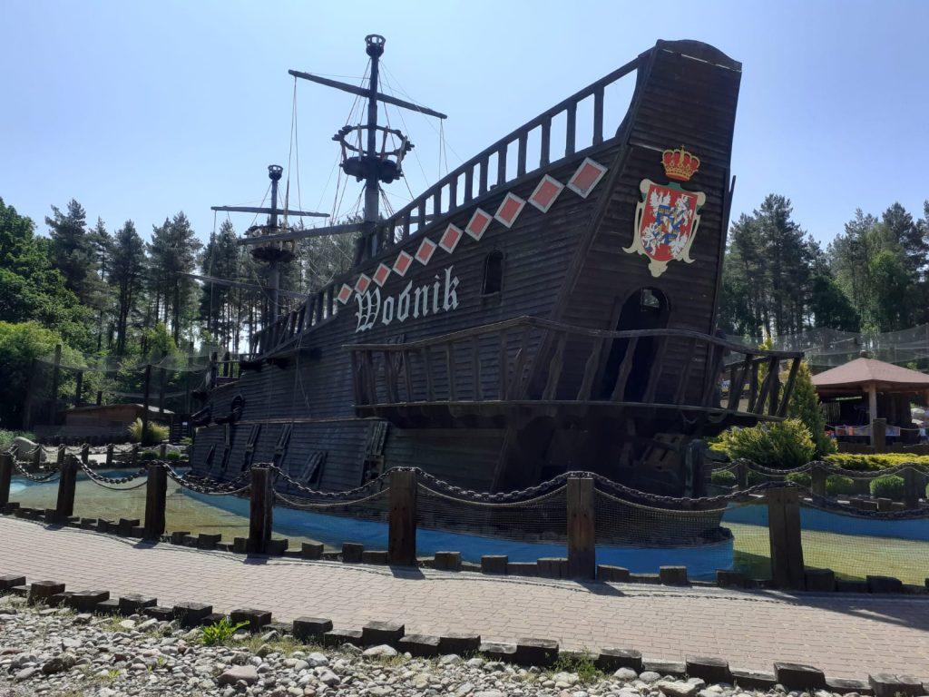 """Duży drewniany statek z napisem """"Wodnik"""" - fotografia wykonana od frontu. Statek posiada dwa wysokie słupy oraz """"gniazdo"""""""
