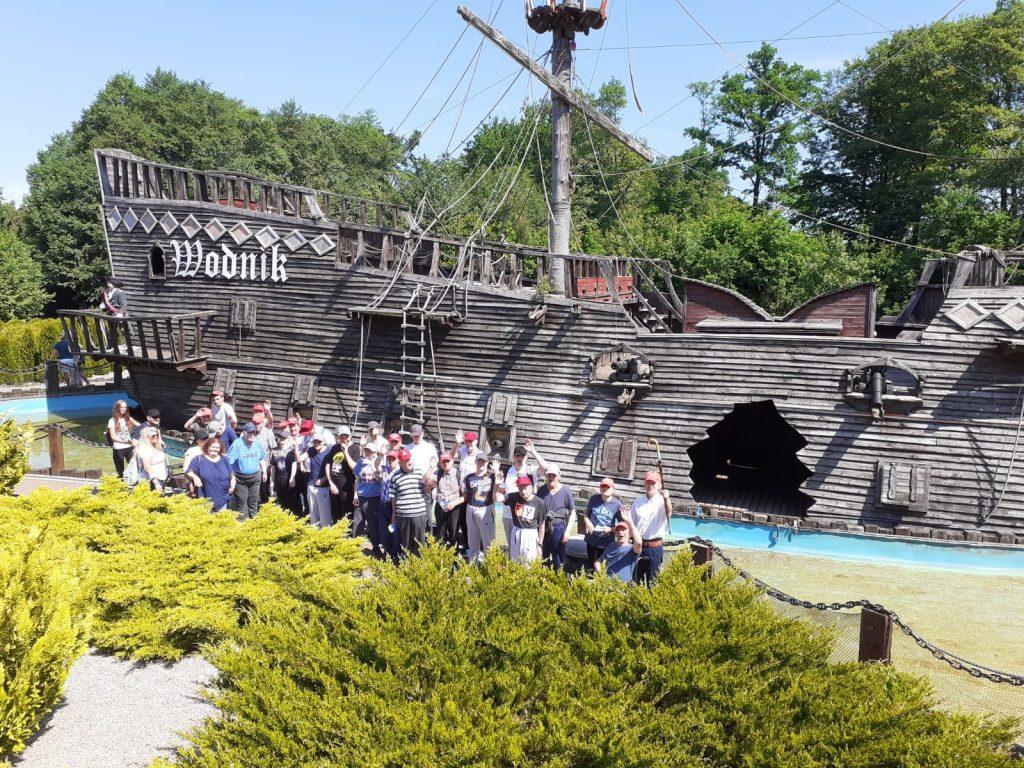 Grupa mieszkańców podczas wycieczki w parku, w tle duża makieta drewnianego statku